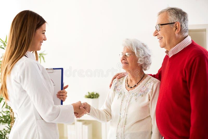 Sorridere e coppie senior felici che visitano un medico fotografia stock libera da diritti
