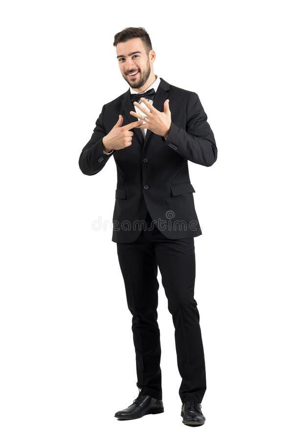 Sorridere felice appena sposo sposato che indica la fede nuziale sul suo dito immagini stock
