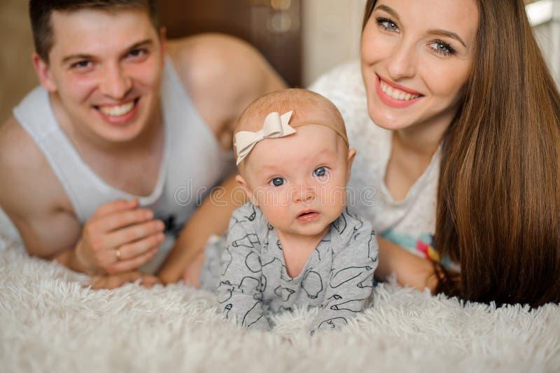 Sorridere felice parents la menzogne sul letto con la ragazza di neonato sveglia immagine stock libera da diritti