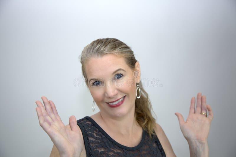 Sorridere femminile biondo maturo con entrambe le mani su immagini stock libere da diritti
