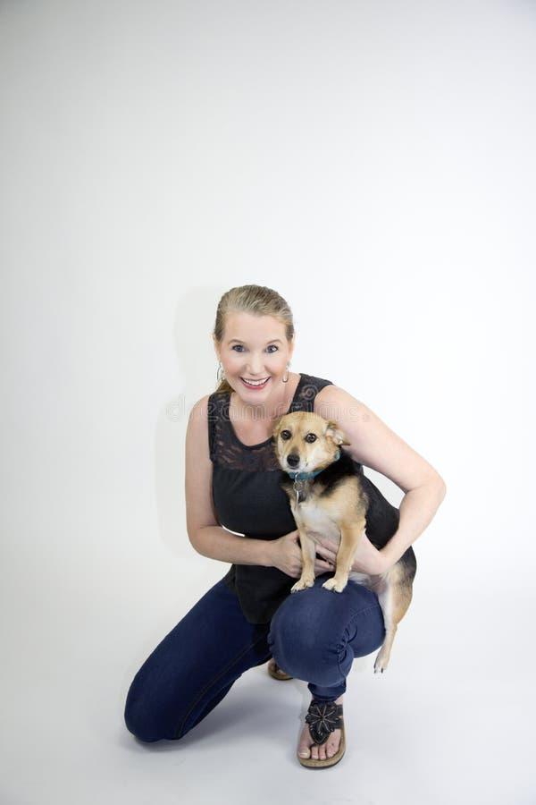 Sorridere femminile biondo maturo con il cane che affronta macchina fotografica fotografia stock libera da diritti