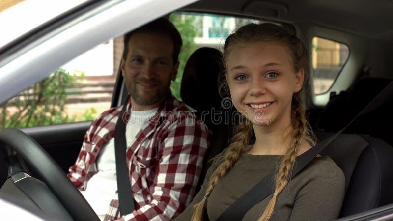 Sorridere femminile felice nella macchina fotografica, sedentesi in automobile con l'istruttore, scuola guida fotografia stock