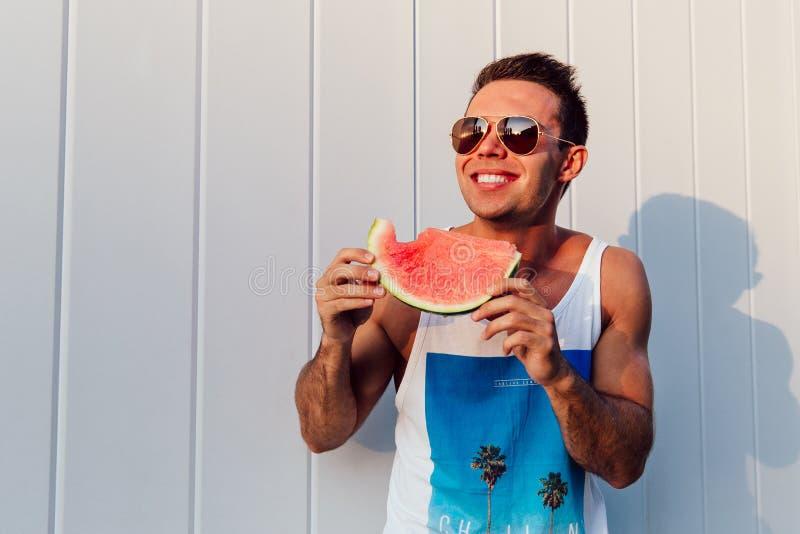 Sorridere mangiatore di uomini un'anguria, all'aperto immagini stock libere da diritti