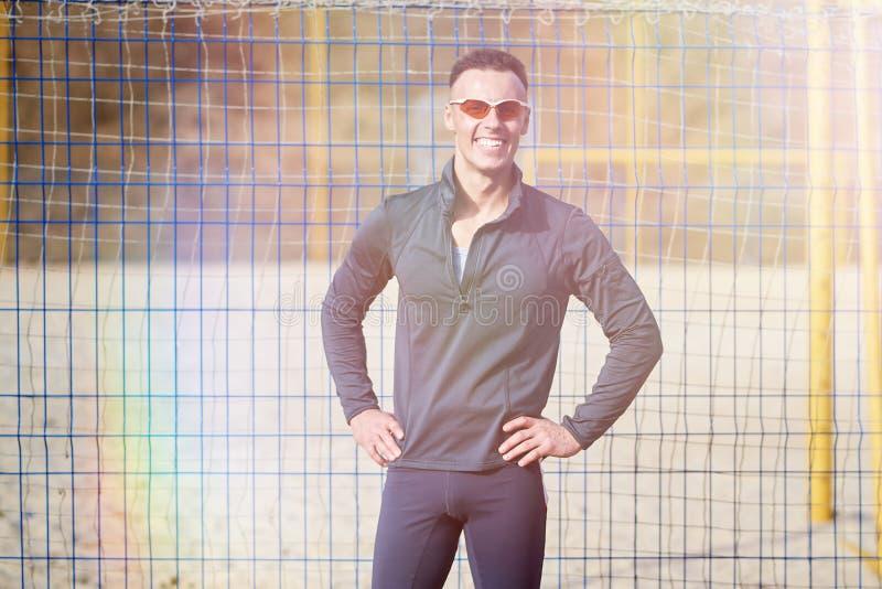 Sorridere maschio atletico davanti ad una griglia immagini stock libere da diritti