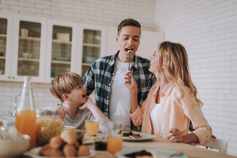 Sorridere positivo del bambino ed il suo marito d'alimentazione della madre con la banana immagine stock