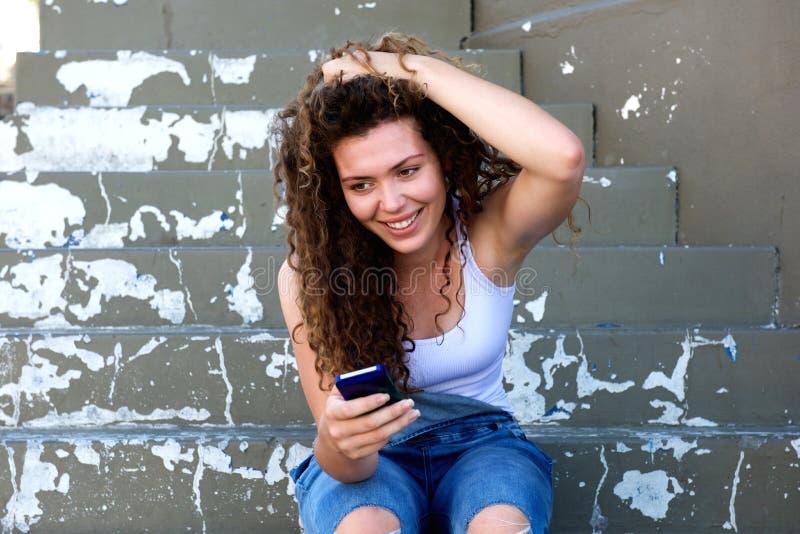 Sorridere teenager con la mano in capelli che si siedono con il cellulare fotografia stock libera da diritti