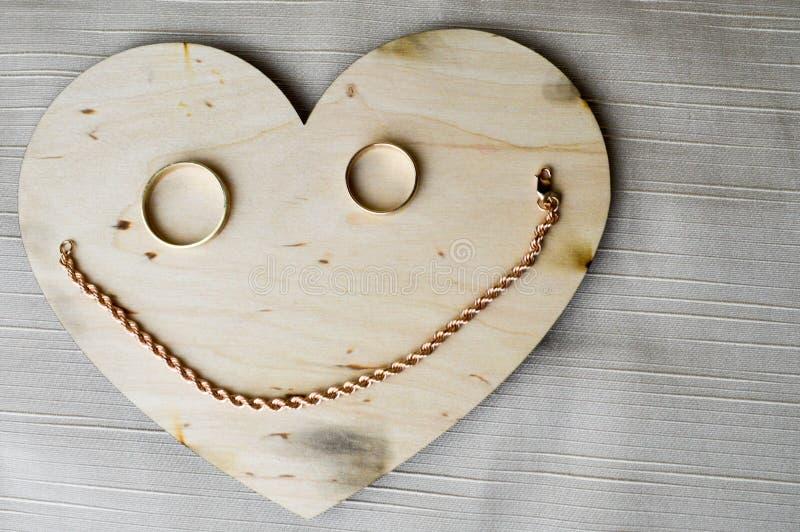Sorridere, una tazza allegra fatta da un cuore di legno al giorno del ` s del biglietto di S. Valentino, gli anelli di oro di noz fotografia stock