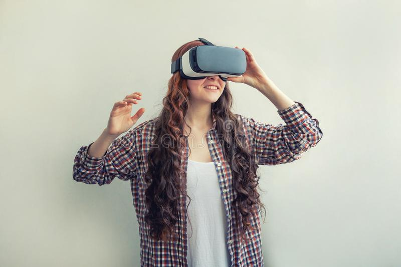 Sorridi giovane donna che indossa l'elmetto degli occhiali da realtà virtuale su fondo bianco Smartphone con fotografia stock libera da diritti