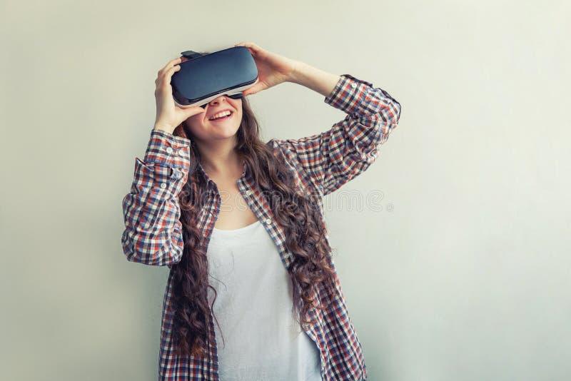 Sorridi giovane donna che indossa l'elmetto degli occhiali da realtà virtuale su fondo bianco Smartphone con fotografia stock