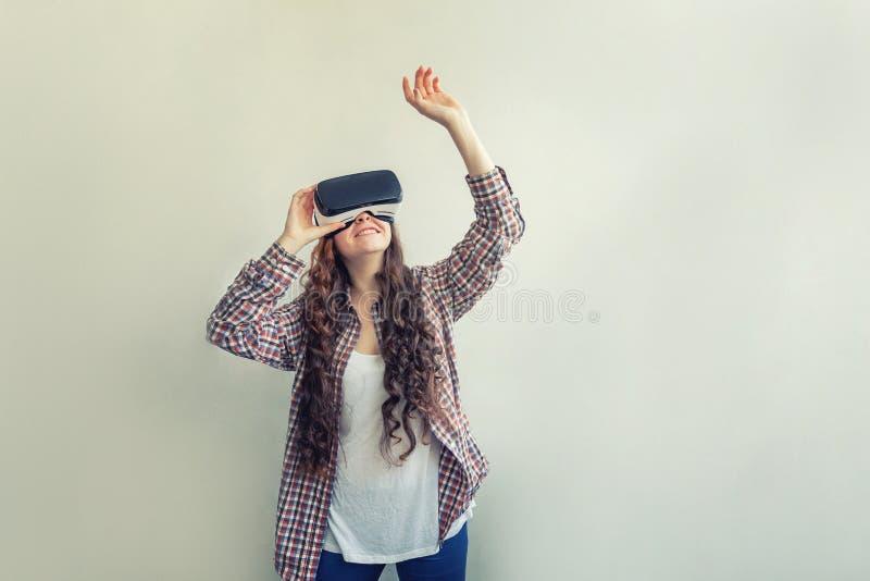 Sorridi giovane donna che indossa l'elmetto degli occhiali da realtà virtuale su fondo bianco Smartphone con fotografie stock