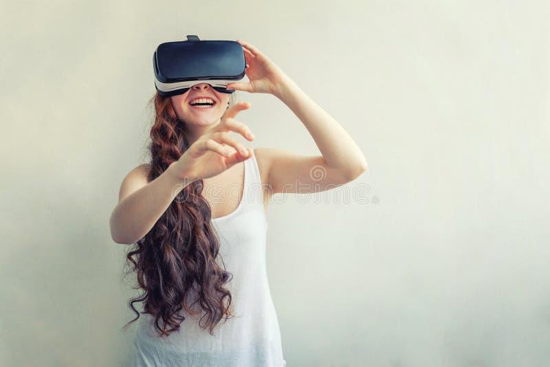 Sorridi giovane donna che indossa l'elmetto degli occhiali da realtà virtuale su fondo bianco Smartphone con immagini stock libere da diritti