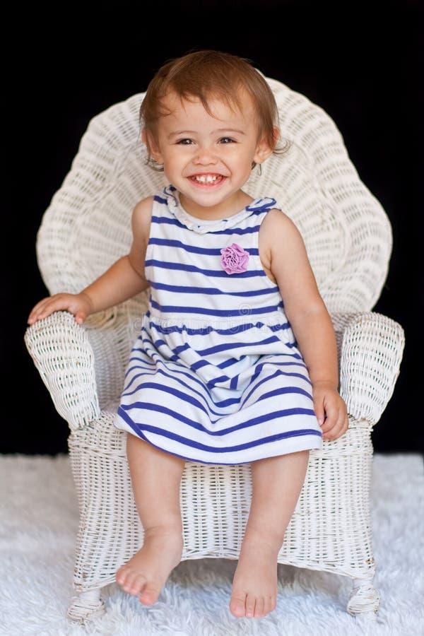 Sorrindo 1 menina multicultural dos anos de idade na cadeira fotos de stock royalty free