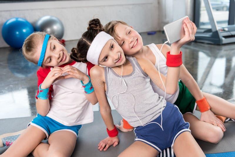 Sorrindo caçoa a tomada do selfie com o smartphone no gym, conceito da escola do esporte das crianças foto de stock royalty free
