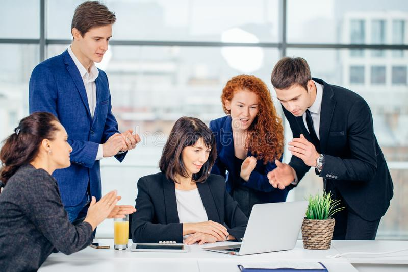 Sorrindo colegas de trabalho masculinos fêmeas e consideráveis que sentam-se na tabela, olhando o portátil foto de stock royalty free