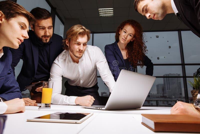 Sorrindo colegas de trabalho masculinos fêmeas e consideráveis que sentam-se na tabela, olhando o portátil imagens de stock royalty free
