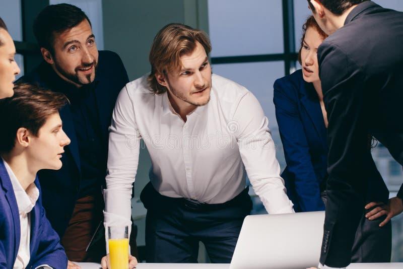 Sorrindo colegas de trabalho masculinos fêmeas e consideráveis que sentam-se na tabela, olhando o portátil imagens de stock