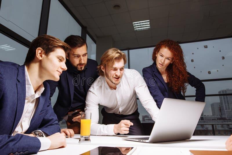 Sorrindo colegas de trabalho masculinos fêmeas e consideráveis que sentam-se na tabela, olhando o portátil fotos de stock royalty free