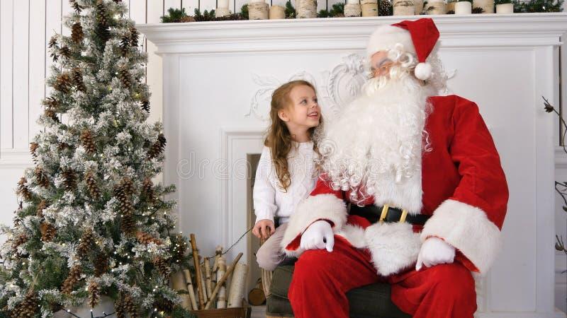 Sorrindo e recue a menina que compartilha de seus sonhos do Natal com a Santa foto de stock royalty free
