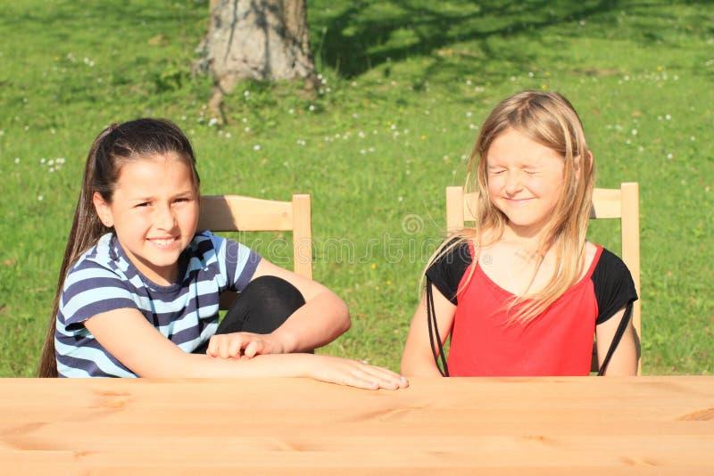 Sorrindo e sorrindo as meninas que sentam-se atrás da tabela imagem de stock royalty free