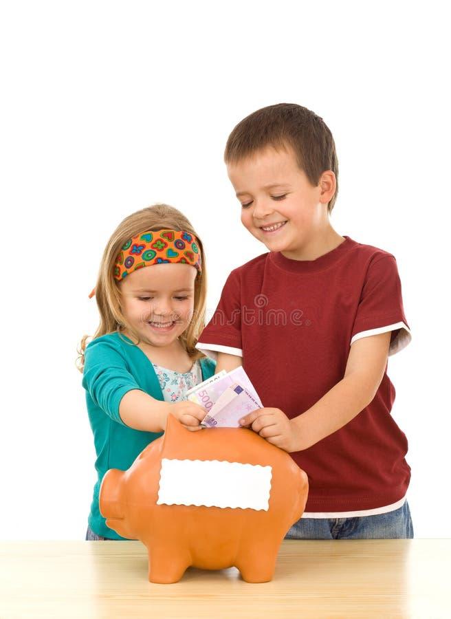 Sorrindo os miúdos que enchem o banco piggy fotos de stock