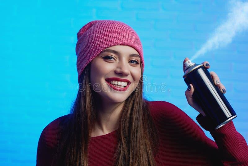 Sorrir chapéu consideravelmente fêmea e camiseta vermelhos vestindo que levantam com pintura pulveriza foto de stock