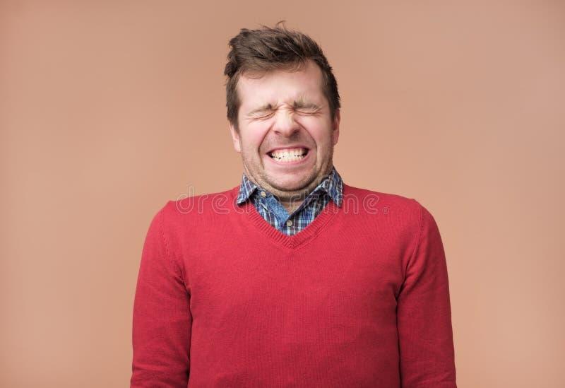Sorrir forçadamente do indivíduo na câmera, mostram os dentes brancos, fecham eyeswaiting para o presente fotografia de stock