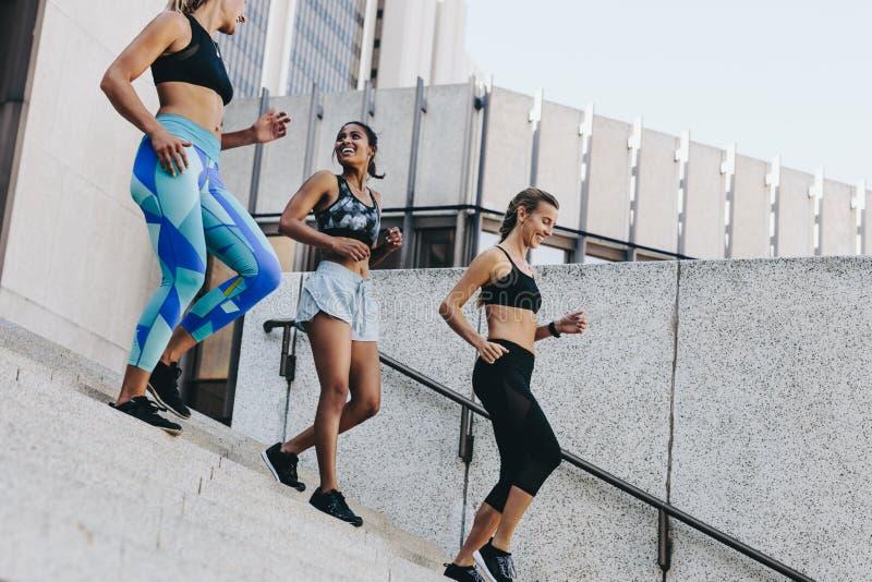 Sorrir mulheres no treinamento veste o passeio abaixo das escadas fotos de stock