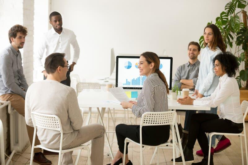 Sorrir os empregados incorporados que falam sobre o trabalho resulta na equipe m foto de stock