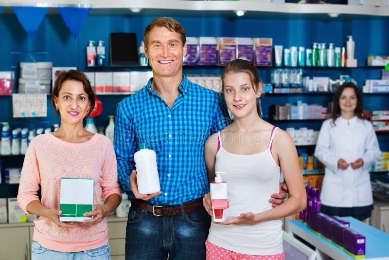 Sorrir parents com o adolescente da menina que guarda bens da farmácia fotos de stock