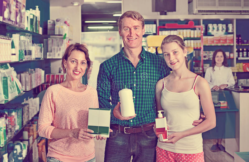 Sorrir parents com o adolescente da menina que guarda bens da farmácia fotos de stock royalty free