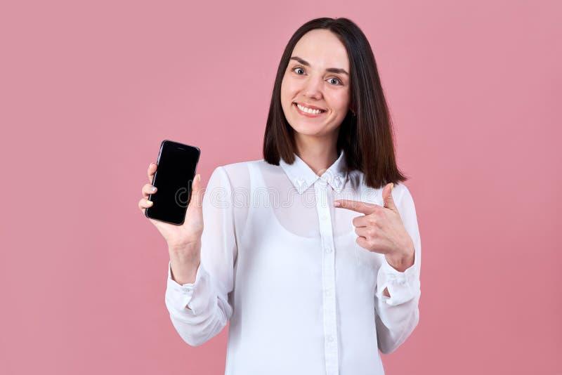 Sorrisi amichevoli della giovane ragazza castana amichevole ampiamente, indicando il suo dito allo smartphone in sua mano fotografie stock
