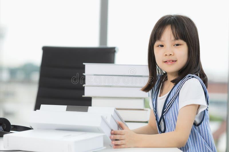 Sorrisi asiatici della ragazza alla macchina fotografica, lei che si siede alla tavola fotografie stock