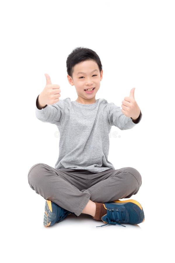 Sorrisi del ragazzo e pollice di mostra su sopra bianco immagini stock