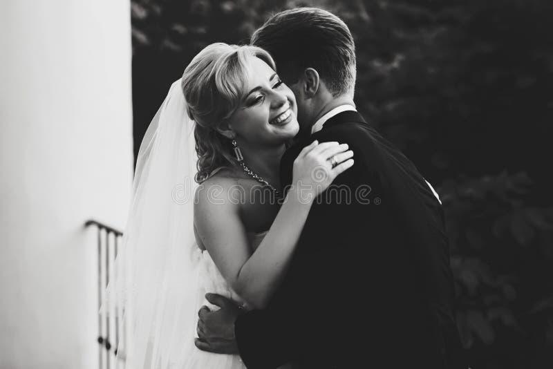 Sorrisi della sposa mentre lo sposo la abbraccia sul balcone immagini stock