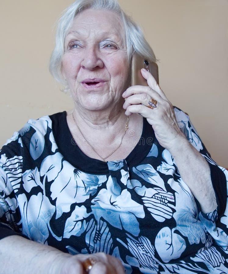 Sorrisi e colloqui di una donna anziana su un telefono cellulare immagini stock