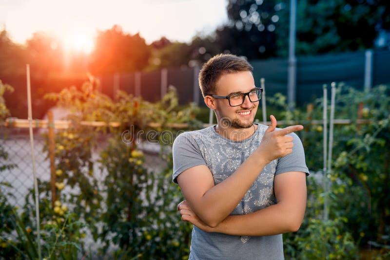 Sorrisi e punti giovani di un tipo un dito voi In parco al tramonto fotografie stock