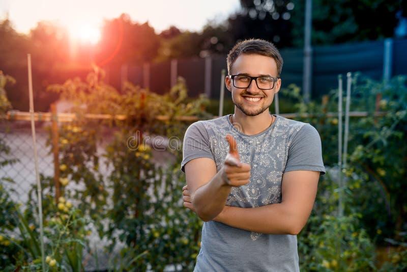 Sorrisi e punti giovani di un tipo un dito voi In parco al tramonto fotografia stock libera da diritti