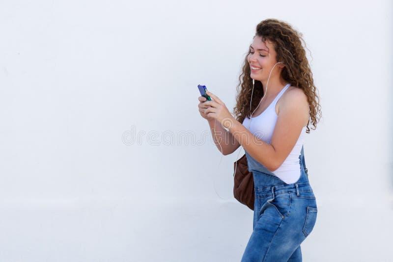 Sorriso adolescente com passeio do telefone celular e dos fones de ouvido foto de stock royalty free