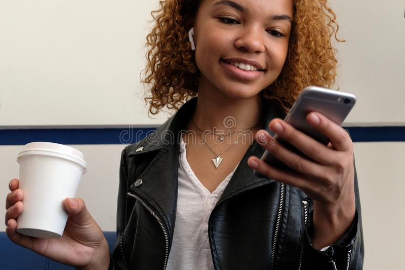 Sorriso afro-americano da menina, olhando em seu telefone Um vidro branco com café à disposição Uma mulher negra moderna nova bon fotografia de stock