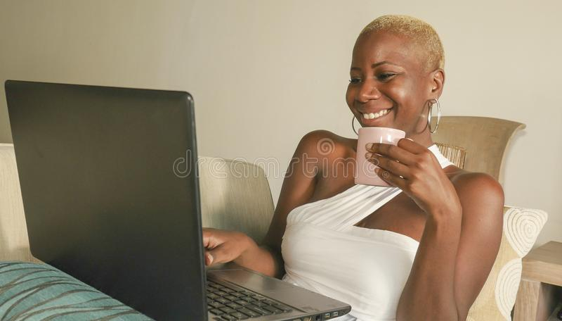 Sorriso afro-americano preto bonito e feliz novo da mulher entusiasmado tendo o divertimento no Internet usando meios sociais no  fotos de stock royalty free