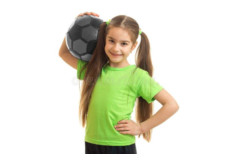 Sorriso alegre da menina com a bola de futebol em suas mãos imagem de stock