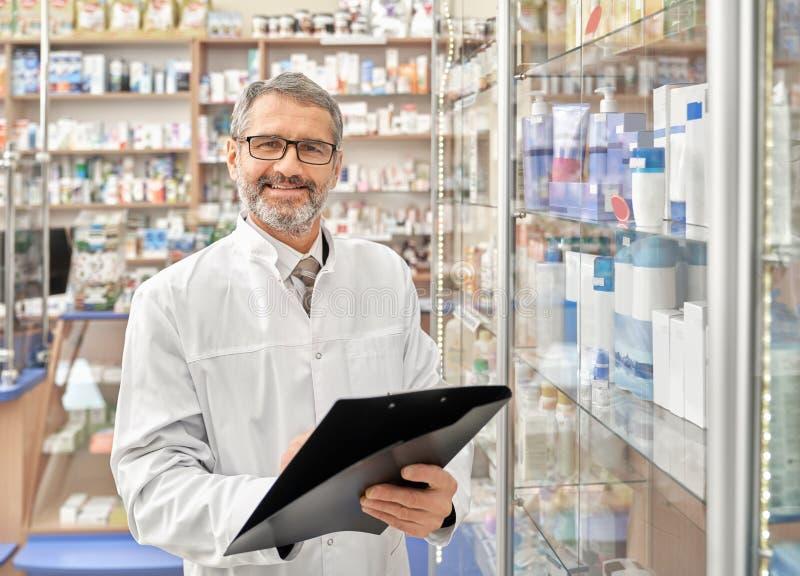 Sorriso alegre do farmacêutico, levantando na drograria imagem de stock