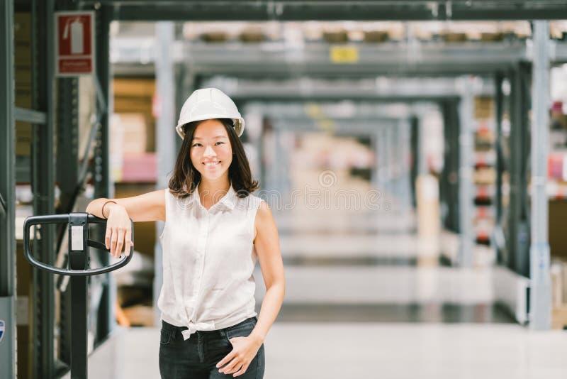 Sorriso asiático novo bonito da mulher do coordenador ou do técnico, fundo do borrão do armazém ou da fábrica, indústria ou conce foto de stock royalty free