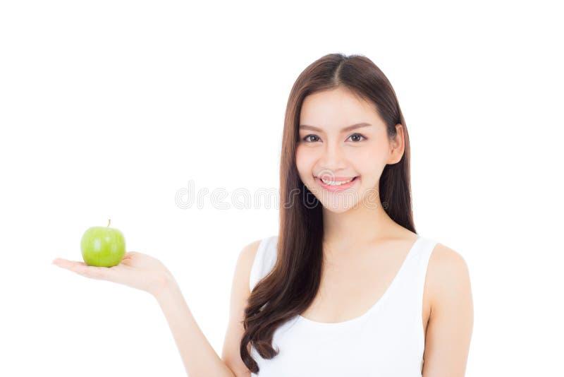 Sorriso asiático novo bonito da mulher e guardar o fruto verde da maçã com bem-estar e saudável isolado imagens de stock royalty free
