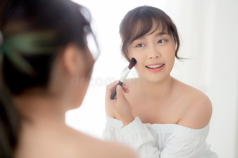 Sorriso asiático novo da mulher do retrato da beleza com a cara que olha o espelho que aplica a composição com o mordente da esco imagens de stock