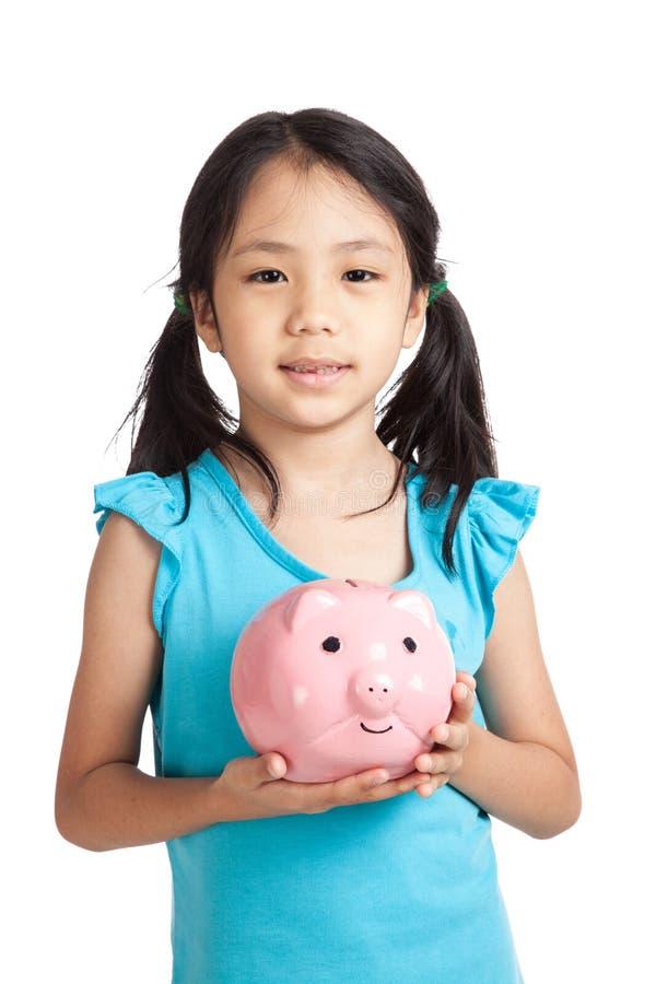 Sorriso asiático pequeno da menina com mealheiro fotos de stock royalty free