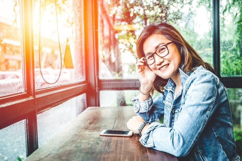 Sorriso asiatico di seduta della donna dei pantaloni a vita bassa del nerd di vetro in caffè delle finestre di vetro immagine stock libera da diritti