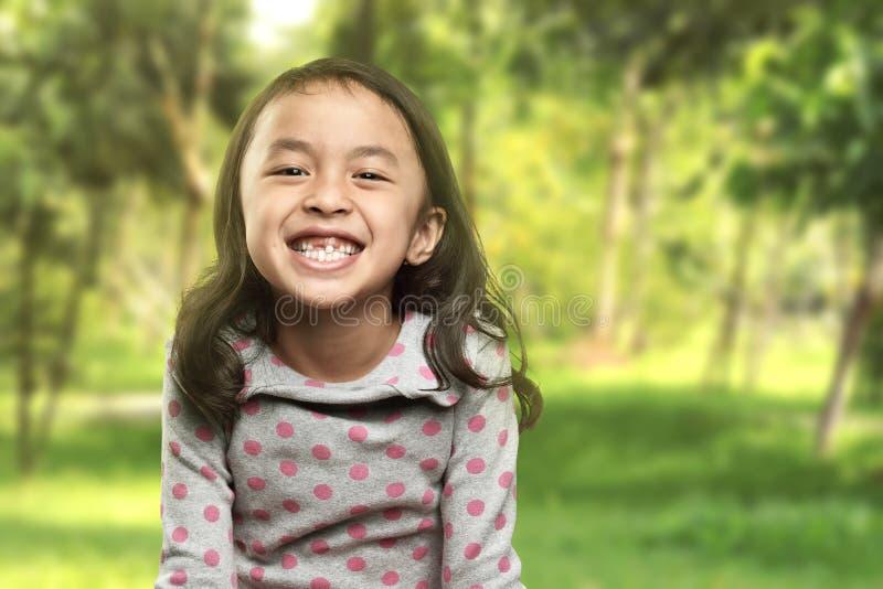 Sorriso asiatico divertente della bambina con il suo dente rotto fotografia stock