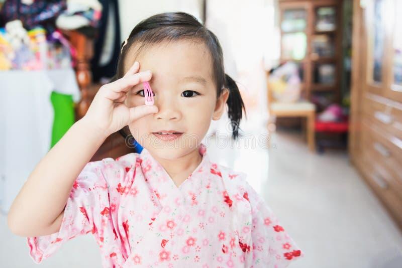Sorriso asiatico dolce del piccolo bambino e tenere la clip di capelli, concetto del condimento dei capelli fotografia stock