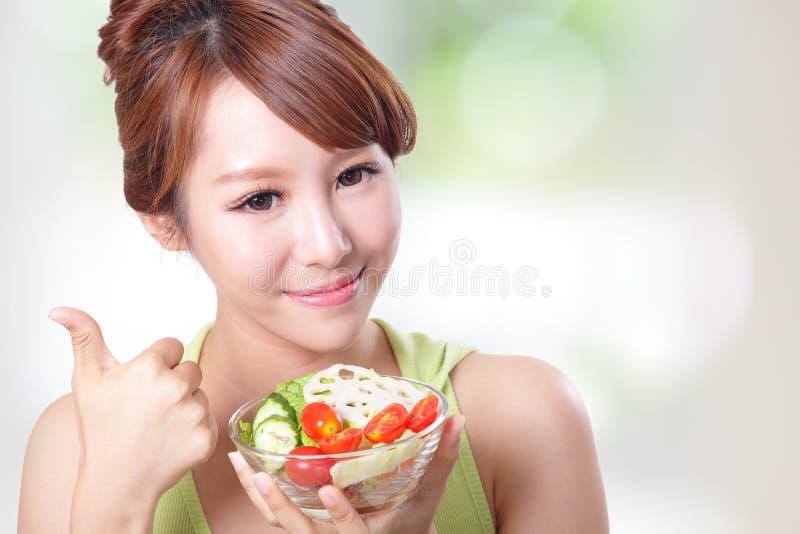 Sorriso attraente della donna che mangia insalata immagine stock libera da diritti